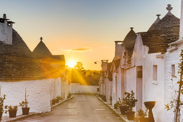 CLKFB124470 Sunrise between trulli houses. Unesco World Heritage Site, Alberobello, Province of Bari, Apulia, Italy