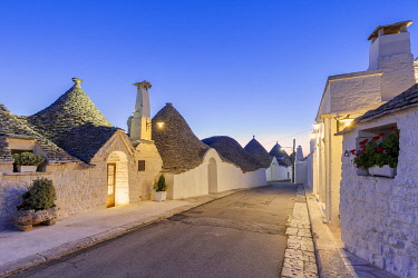 CLKFB124478 Alley between white trulli houses at dusk. Unesco World Heritage Site, Alberobello, Province of Bari, Apulia, Italy