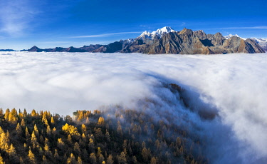 CLKFB125976 Fog covers the Valmalenco(Val Malenco) with the mountain range of Disgrazia in the background. Valtellina, Lombardy, Italy