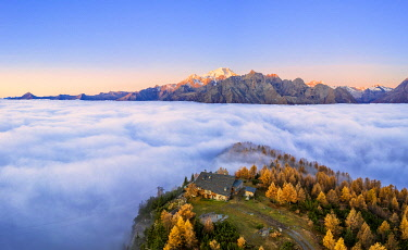 CLKFB125978 Fog covers the Valmalenco(Val Malenco) with the mountain range of Disgrazia illuminated by sunrise in the background and the Motta mountain hut in the foreground. Valtellina, Lombardy, Italy