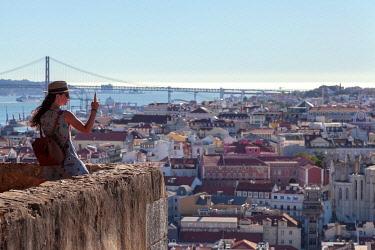 CLKDC122755 A woman while photographing Lisbon from the panoramic terrace of Castelo de Sâ��ÂA?o Jorge (St George's Castle), Alfama Neighborhood, Lisbon, Lisbon Metropolitan Area, Portugal