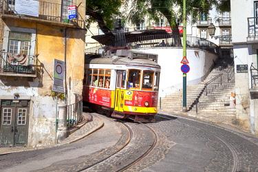 CLKDC122782 A traditional yellow tram in the streets of Alafama Neighborhood, Lisbon, Lisbon Metropolitan Area, Portugal
