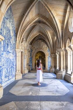 CLKDC124534 A woman admires the cloister arcades of Porto Cathedral (Sao do Porto), Porto, Porto district, Norte Region, Portugal