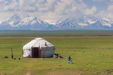 CLKGM128974 Kyrgyzstan landscape with a Yurt and children in foreground and Pamir mountains in the background. Sary Tash, Kyrgyzistan, Central Asia.