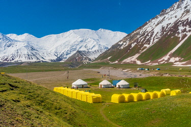 CLKGM128988 The tents of peak Lenin base camp with Lenin peak in the background. Pamir, Kyrgyzstan, Central Asia.