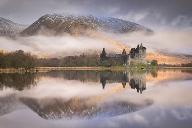 SCO35668AW The ruins of Kilchurn Castle reflected in Loch Awe at dawn on a misty morning in the Scottish Highlands, Argyll and Bute, Scotland.
