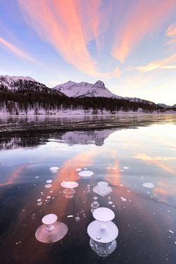CLKFB125074 Methane bubbles in the icy surface of Silsersee with snowy peak illuminated by sunset light. Lake Sils, Engadin Valley, canton of Graubunden, Switzerland