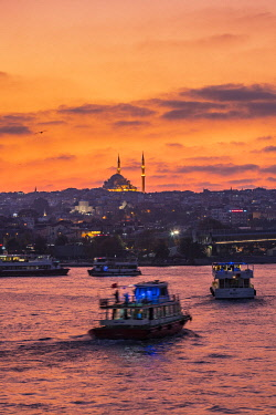CLKGM127801 Boats in the Golden Horn at sunset with a Mosque in the background. Istanbul, Turkey