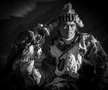 IBLBAY05115726 Mongolian eagle hunter poses with eagle with hood, Bajan-Olgii Province, Mongolia, Asia