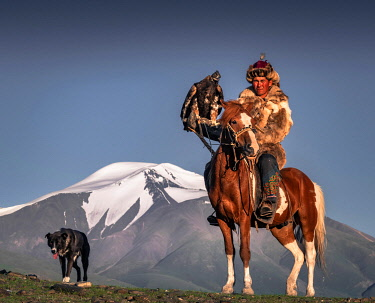 IBLBAY05238783 Mongolian eagle hunter, Kazakh on horseback with trained eagle in front of snow-covered mountains, Bajan-Olgii province, Mongolia, Asia