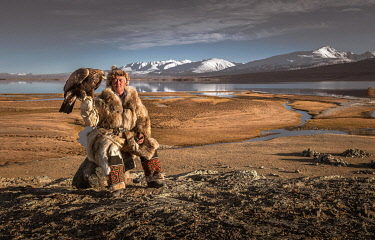 IBLBAY05238801 Mongolian eagle hunter posted with lake in front of landscape with lake and snow-covered mountains, Bajan-Olgii province, Mongolia, Asia