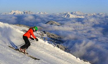 IBLMMW05106993 Female skier descending steep slope, black slope, mountains behind, SkiWelt Wilder Kaiser, Brixen im Thale, Tyrol, Austria, Europe