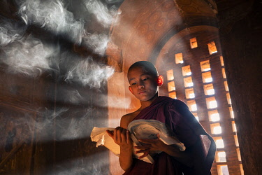 MYA2620AW A young monk reading by a window inside a temple, UNESCO, Bagan, Mandalay Region, Myanmar