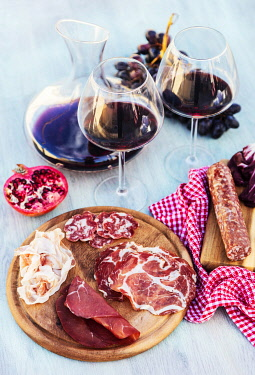 ITA15453 Northern Italy. Emilia Romagna. Several cuts of cured meats including salami, culatello and bresaola, and prosciutto di Parma accompanied by two glasses and a decanter with red wine, pomegranate, grap...
