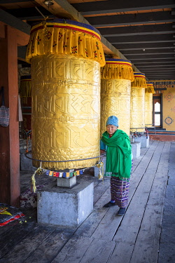 Woman spinning prayer wheels at the National Memorial Chhorten, Thimphu, Bhutan