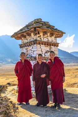 BHU1910AW Novice Monks (Child Monks) standing in front of a stupa in Phobjikha Valley, Bhutan