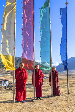 BHU1914AW Novice Monks (Child Monks) standing in front of prayer flags in Phobjikha Valley, Bhutan
