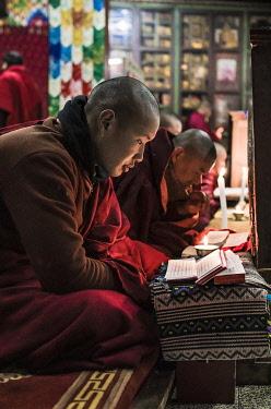 BHU1945AW Monks during evening candle light prayer in Lhodrak Kharchu monastery, Jakar, Bumthang District, Bhutan