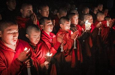 BHU1950AW Monks during evening candle light prayer in Lhodrak Kharchu monastery, Jakar, Bumthang District, Bhutan
