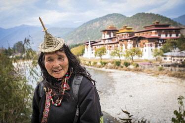 BHU1956AW A Bhutanese woman in front of Punakha Dzong, Punakha, Punakha District, Bhutan