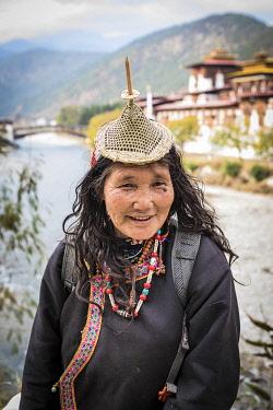 BHU1957AW A Bhutanese woman in front of Punakha Dzong, Punakha, Punakha District, Bhutan