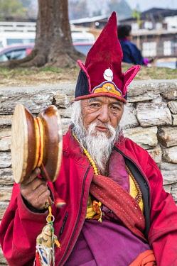 BHU1963AW A priest sitting outside Punakha Dzong, Punakha, Punakha District, Bhutan