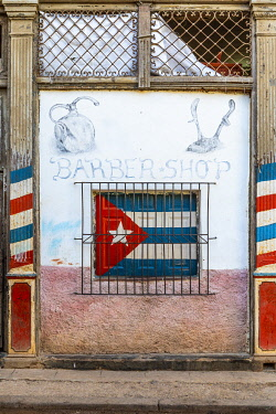 CUB2315AW Cuban flag painted on the window of a barber shop in La Habana Vieja (Old Town), Havana, Cuba