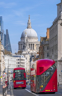 ENG16917AW United Kingdom, England, London, City of London. Red London double-decker buses on Fleet Street with the dome of St. Paul's cathedral in the distance