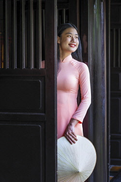 VIT1787AW Southeast Asia, Vietnam, Hue historical city and world heritage site, A young woman in a traditional Vietnamese Ao Dai dress looking out through teak wood doors in a local house, MR