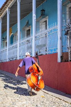 CUB2494AW A man carrying a cello in Plaza Mayor in Trinidad, Sancti Spiritus, Cuba