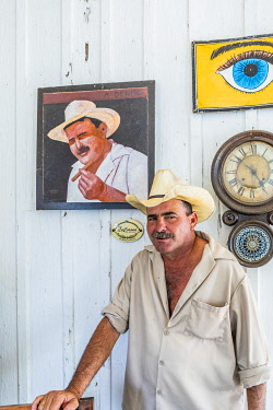 CUB2548AW A tobacco farmer standing in front of his painted portrait in his house in Vinales, Pinar del Rio Province, Cuba