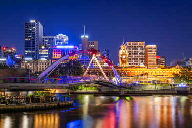 AUS4388AW Clourful lights of the city, Flinders Street Station  and Evan Walker Bridge reflect in the Yarra River. . South Bank, Melbourne, Victoria, Australia