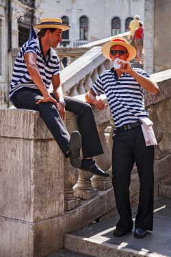 ITA15511 Native gondoliers take a break at the Rialto Bridge, San Polo, Venice, Venteo, Italy.