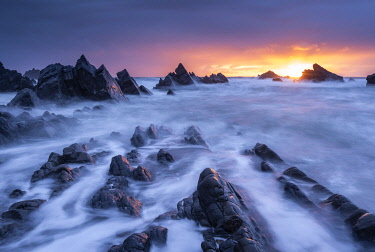 ENG17150AW Sunset over the dramatic rocky shores of Hartland Quay, Devon, England. Spring