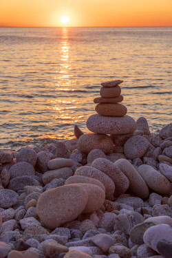 ITA15561AW europe, Italy, Tuscany, Elba Island, a sunset at Pomonte beach with pebble cairns