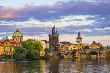 CZE2319AWRF Charles Bridge and Church of Saint Francis of Assisi with Old Town Bridge Tower against sky at sunset, Prague, Bohemia, Czech Republic