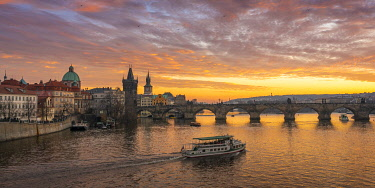 CZE2304AW Boat going towards Charles Bridge and Church of Saint Francis of Assisi with Old Town Bridge Tower at sunset, Prague, Bohemia, Czech Republic
