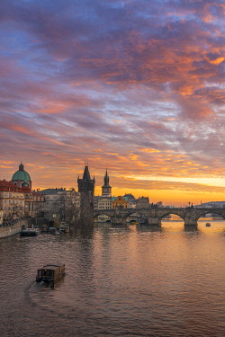 CZE2305AW Boat going towards Charles Bridge and Church of Saint Francis of Assisi with Old Town Bridge Tower at sunset, Prague, Bohemia, Czech Republic