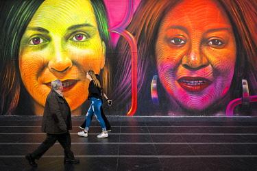 SPA9793AW Pedestrians passing by street art mural NosotrasJuntas by Madrid artist Spok Brillo on Gran Via in Madrid, Community of Madrid, Spain