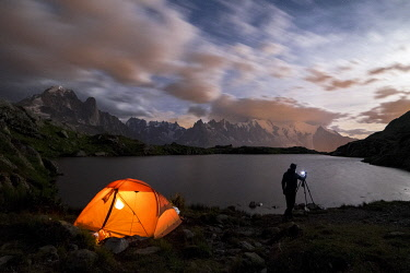 CLKAB130312 Tent and photographer in front of Mont Blanc from Lac de Chesery during summer night, Haute Savoie, France, Europe (MR)