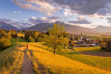 CLKEV133018 A woman staring at the little village of Vill at sunset with the Saile mountain in the background, Vill, Innsbruck, Tyrol, Austria, Europe