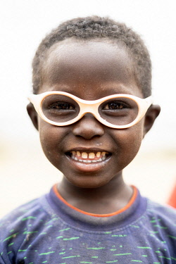 CLKRM132951 Cute little boy with glasses smiling at camera, Melabday, Asso Bhole, Danakil Depression, Afar Region, Ethiopia, Africa