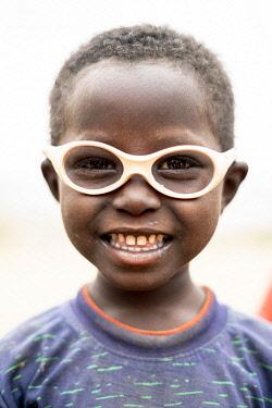 CLKRM132951 Cute little boy with glasses smiling at camera, Melabday, Asso Bhole, Danakil Depression, Afar Region, Ethiopia, Africa