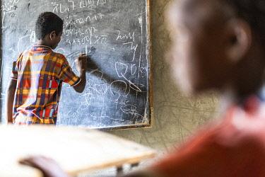 CLKRM132955 Young boy writing on blackboard at school, Melabday, Asso Bhole, Danakil Depression, Afar Region, Ethiopia, Africa