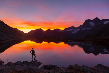 CLKGM130700 Sunsetscape of an hiker at Confinale pass lake during a summer sunset. Confinale pass lake, Valmalenco valley, Sondrio district, Valtellina, Alps, Lombardy, Italy, Europe.