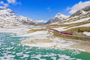 CLKAB132218 Bernina Express train at Lago Bianco during thaw, Bernina Pass, canton of Graubunden, Engadine, Switzerland