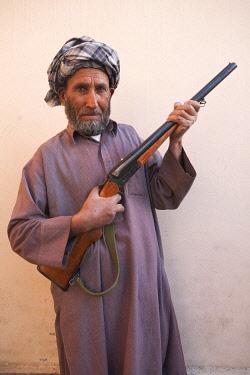AFG0004AW A bearded man in a headscarf holdling a rifle, Kabul, Afghanistan