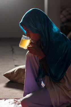 AFG0006AW A girl wearing a headscarf sips tea from a glass in an orphanage, Kabul, Afghanistan