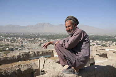 AFG0007AW An elderly, bearded man wearing a Chitrali cap crouches as he looks out over the city, Kabul, Afghanistan