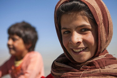 AFG0011AW A girl smiles while playing with friends, Kabul, Afghanistan